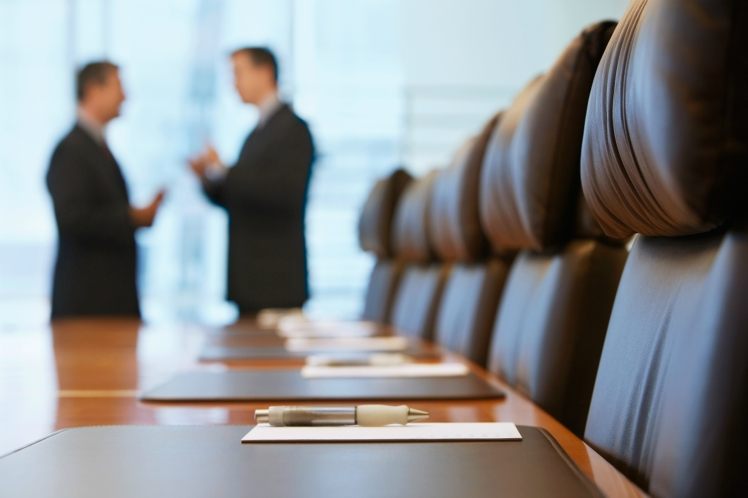 shutterstock_144792676-Side-view-of-two-blurred-businessmen-talking-in-conference-room-web